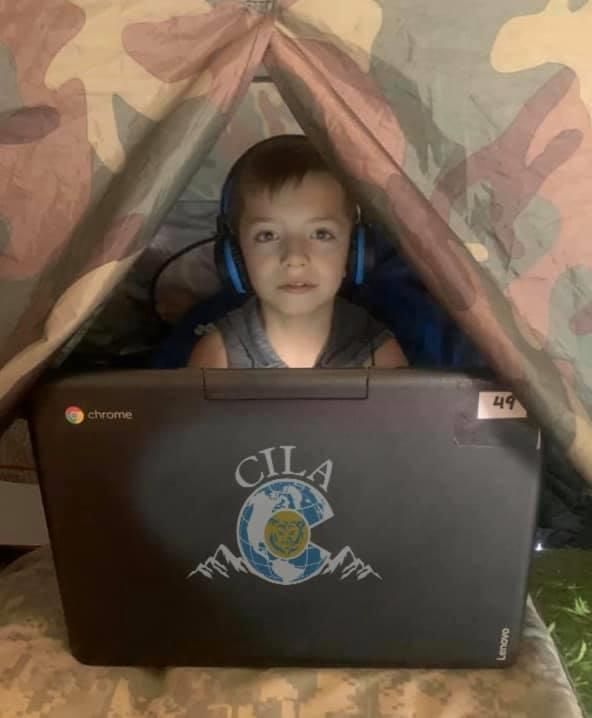 A student learns from home using a CILA laptop