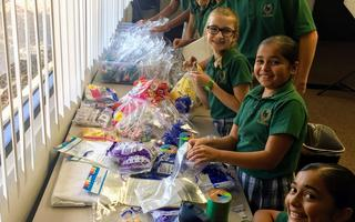 students packaging candy and toys into small decorative bags