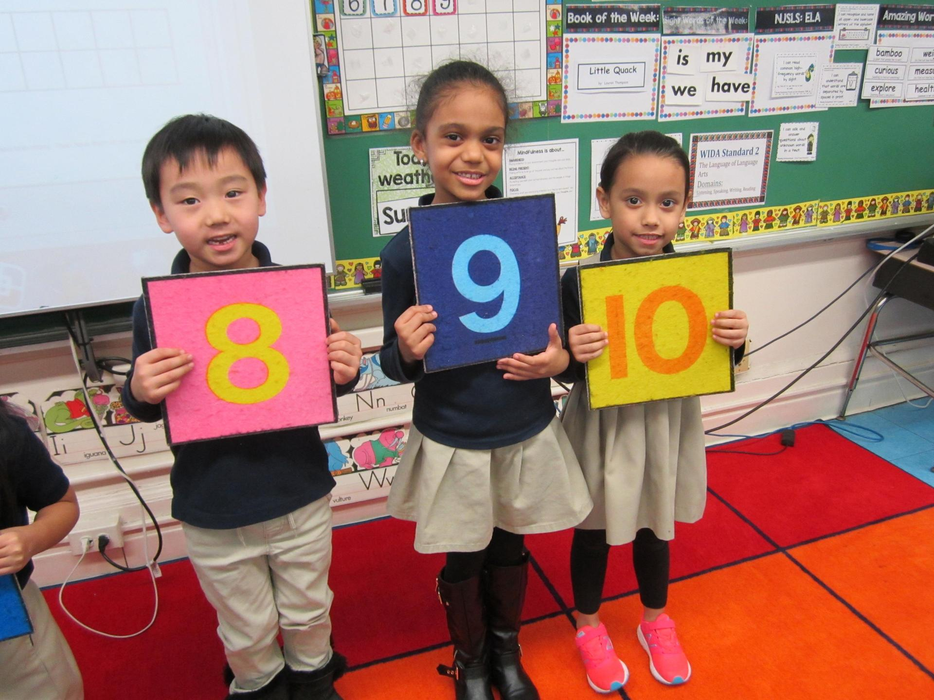 kids holding signs for numbers 6-9