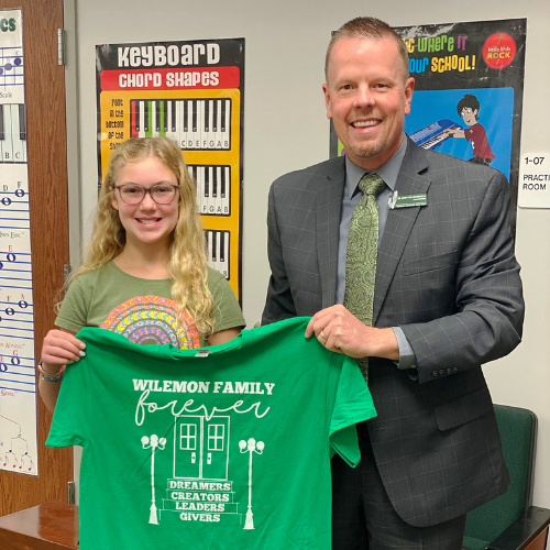 superintendent and young girl both holding a t shirt