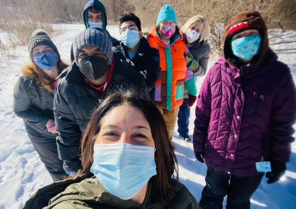 young adults outside at park with teacher in the snow with masks on