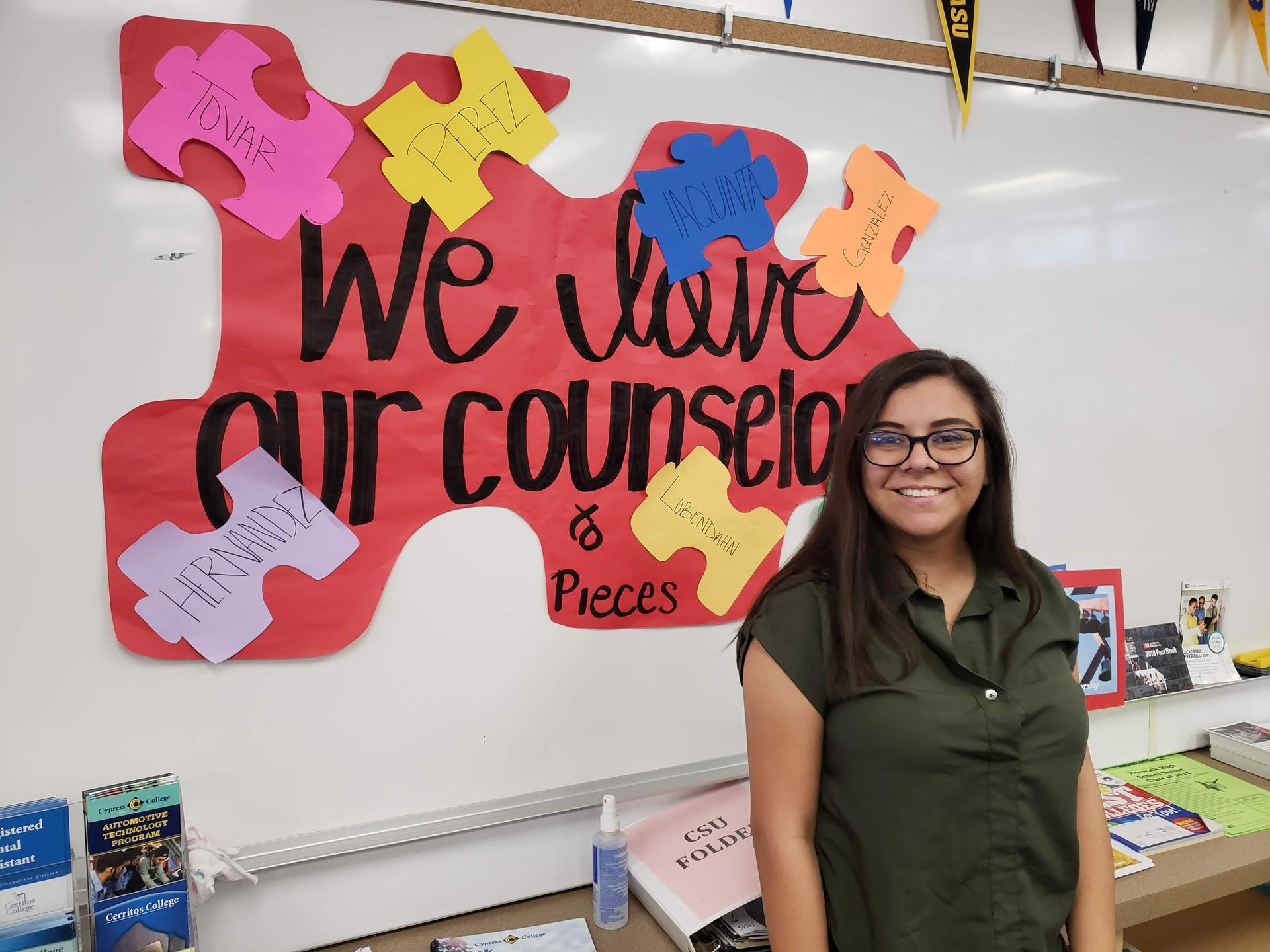 Mrs. Cuevas in front of a 'We love our counselors' poster