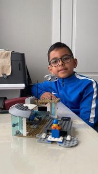 boy with futuristic looking lego house he built
