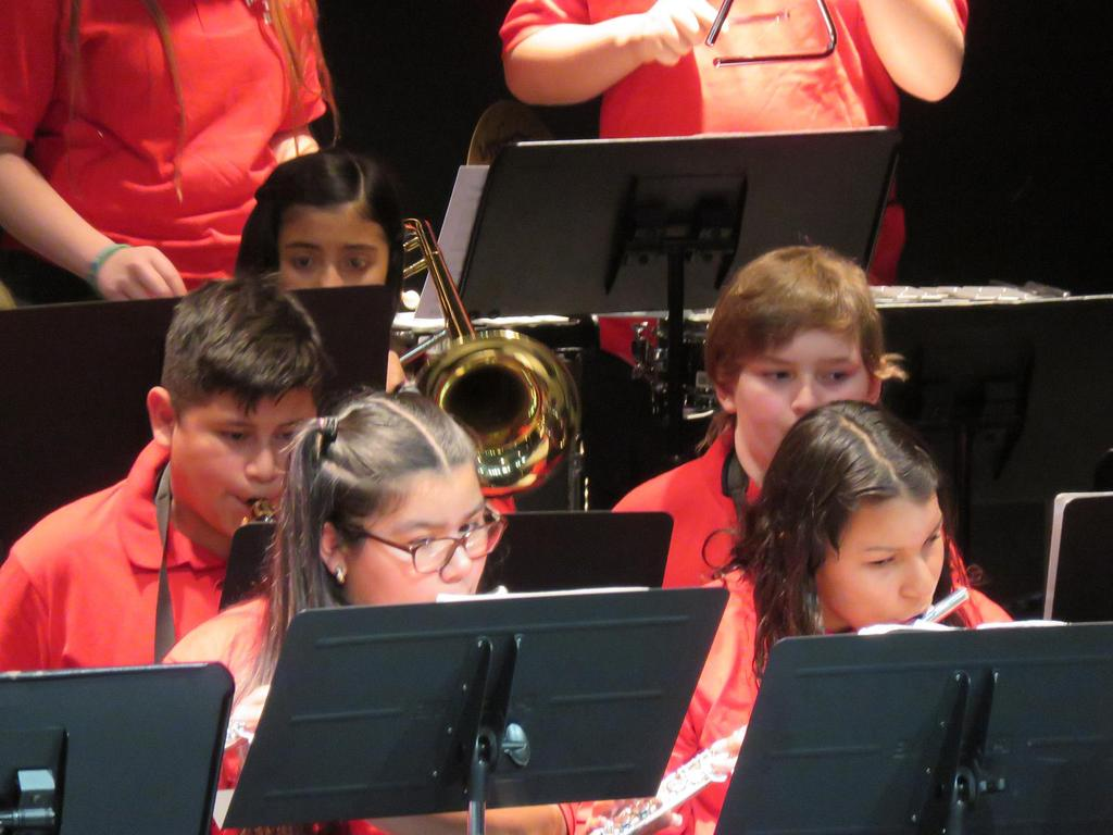 A close-up of four middle school band members during the middle of a number