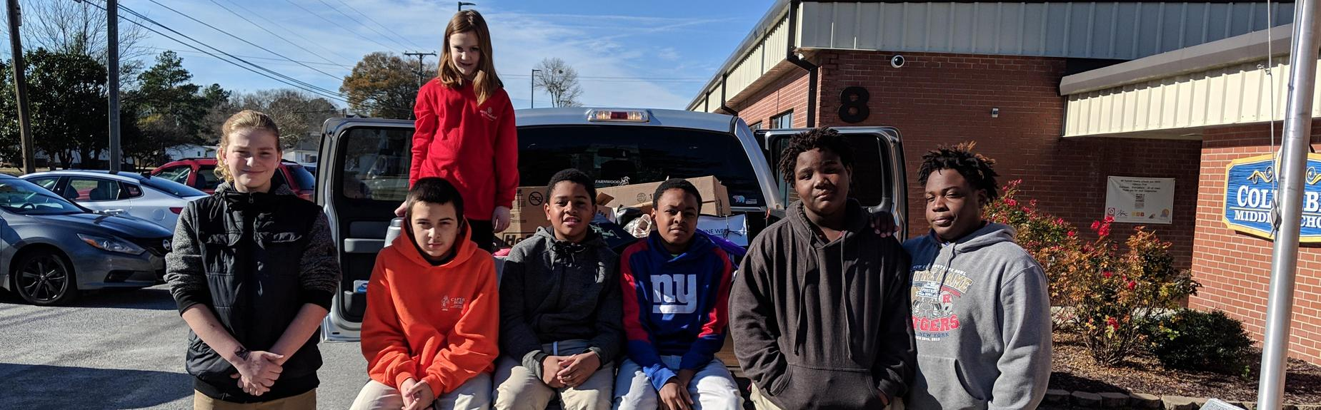 volunteer students sitting in truck bed