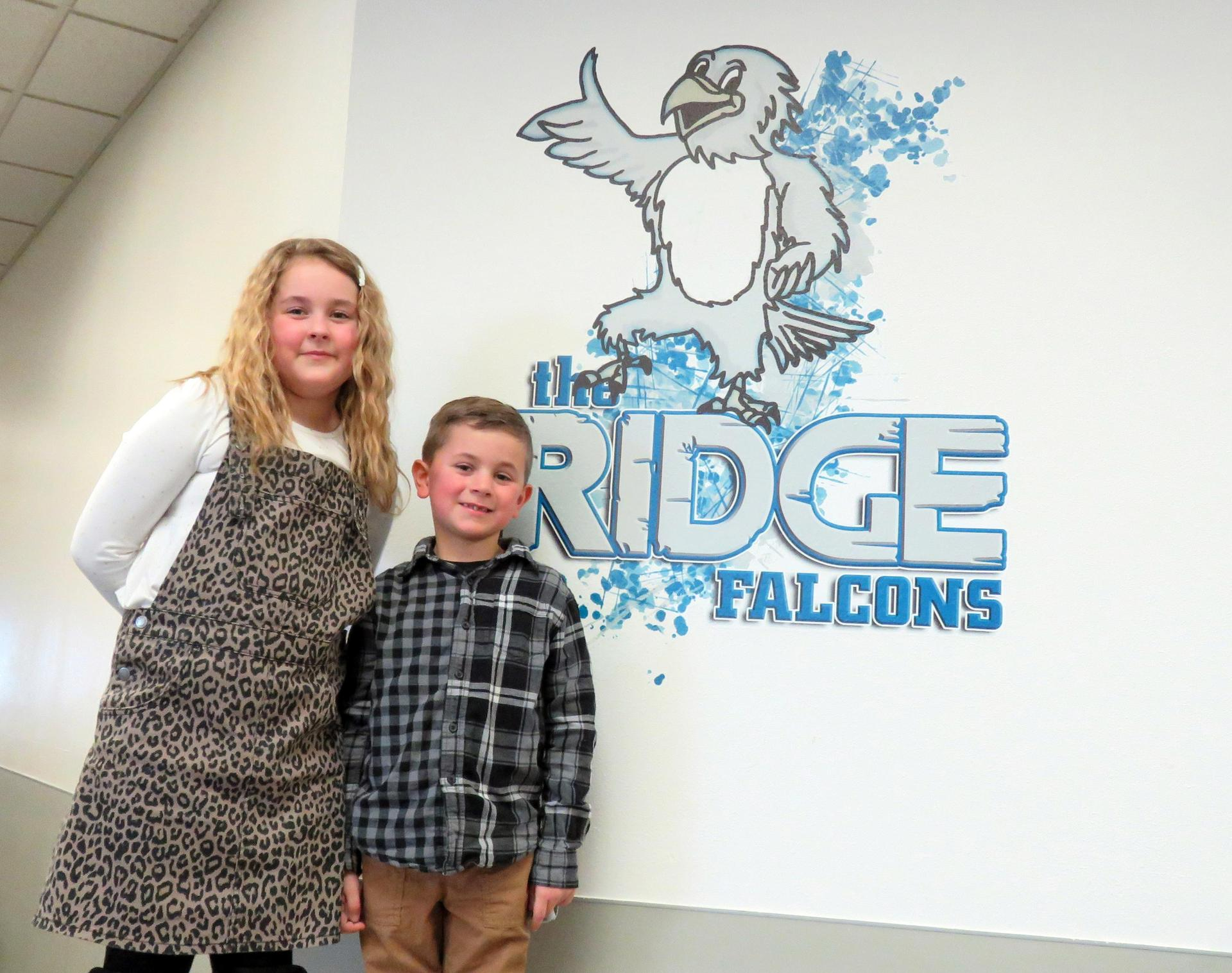 A girl and boy pose in front of the Park Ridge falcon logo