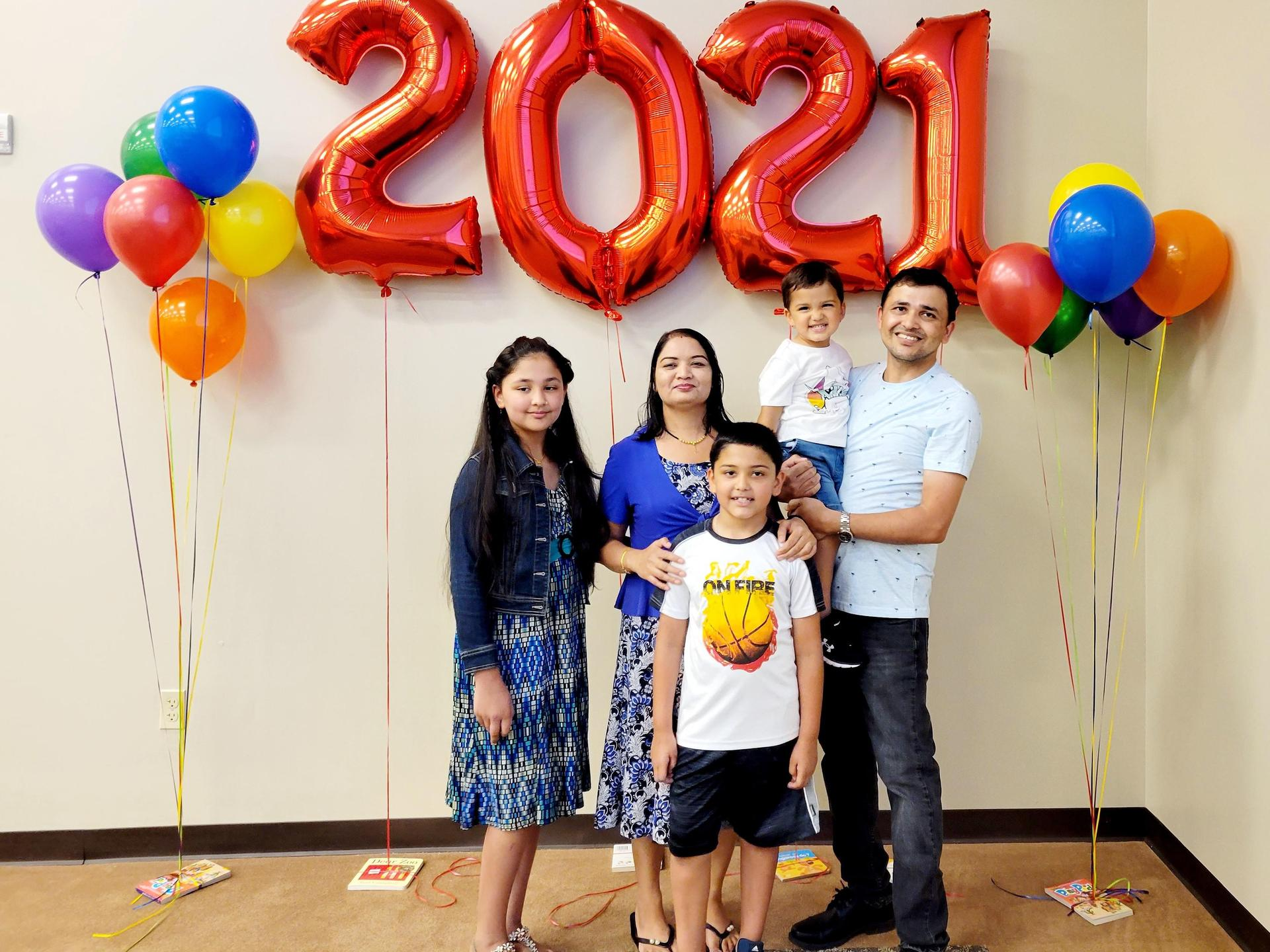 Family stands in front of the 2021 graduation balloon banner