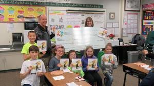 Teacher Laura Crawford and Principal Steve LaBau pose with children and a grant check from the Nampa Schools Foundation.