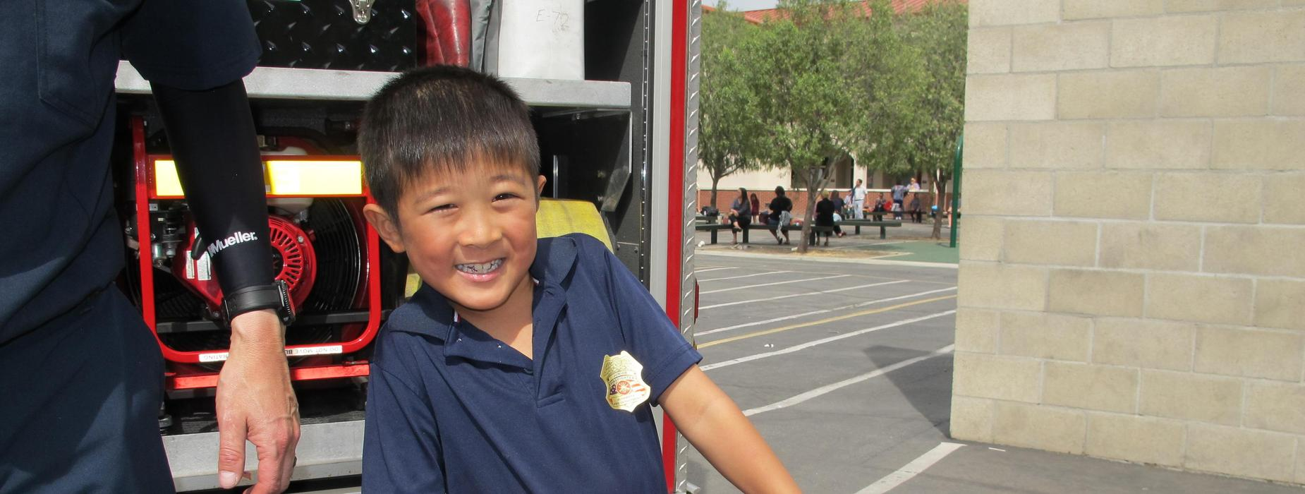 Marguerita student wearing a Firefighter badge