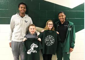 two varsity basketball players pose with elementary age ball boy and girls
