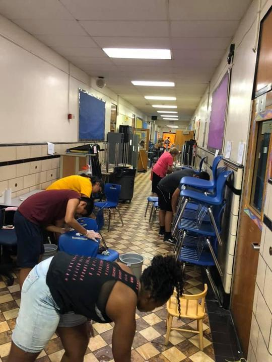 students and staff cleaning the chair placed in the classroom hallways