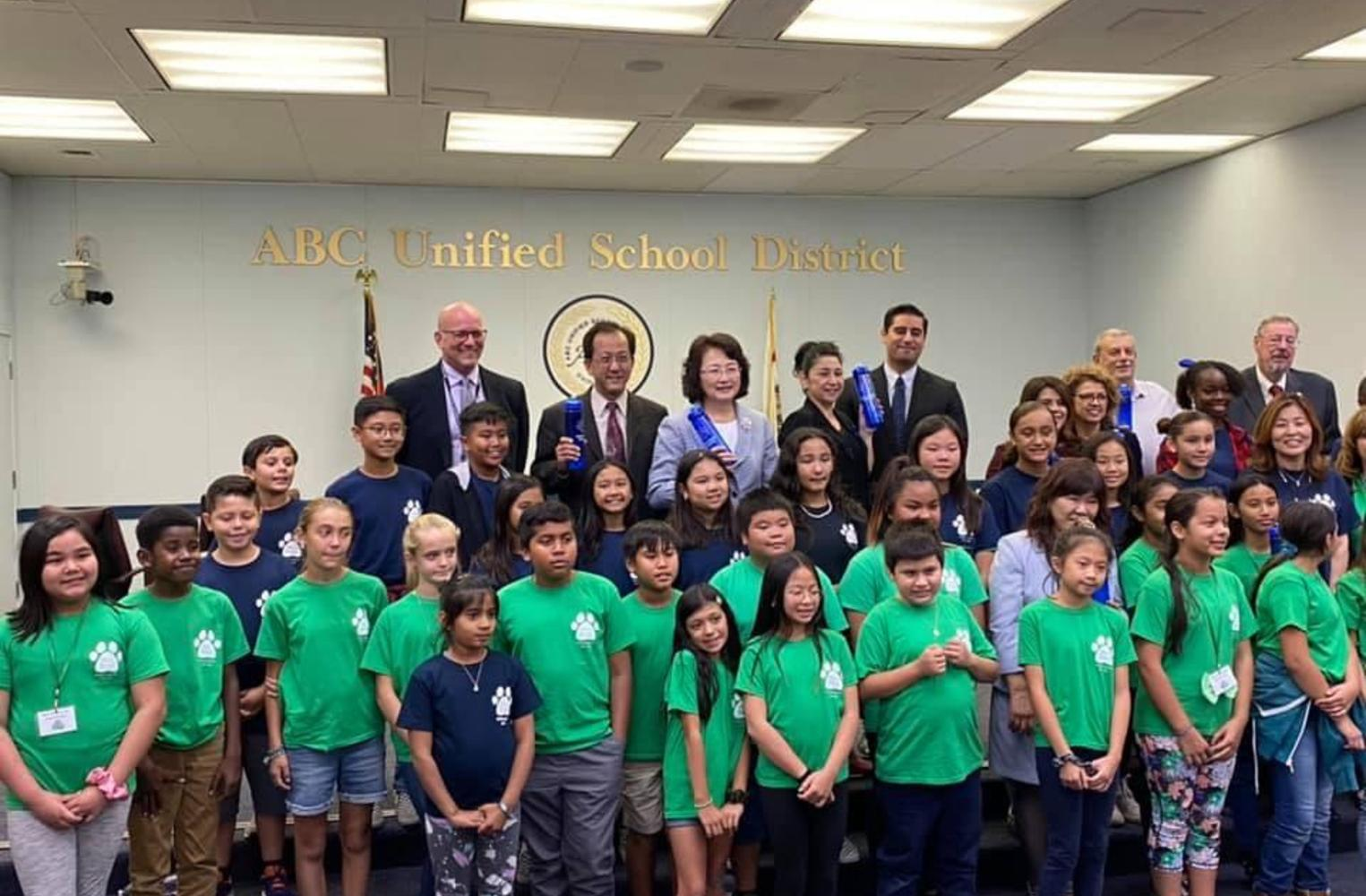 student wearing green tshirts and school board members standing together in front of the united states flag