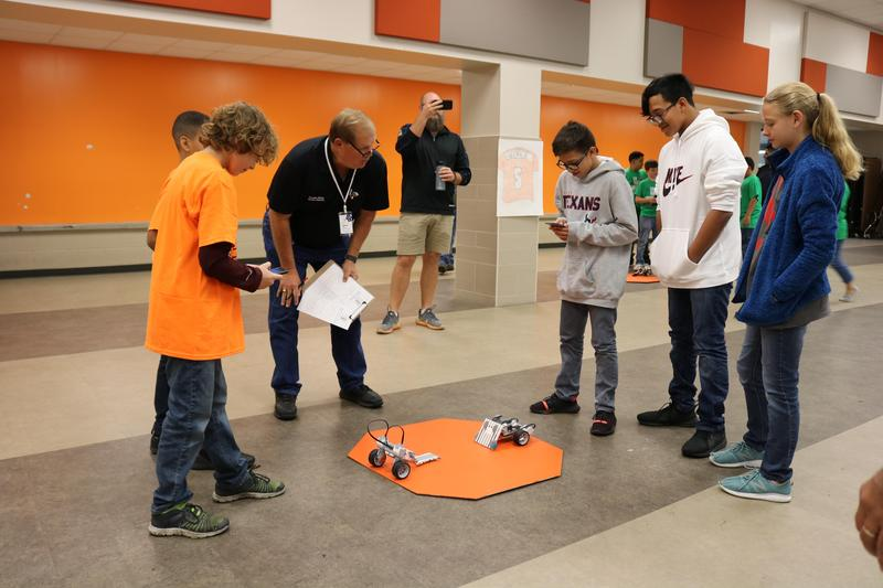 Students standing and operating their robots