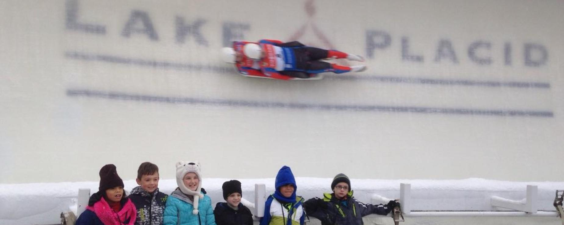 A group of elementary students bundled up in big jackets visiting the Lake Placid Olympic center.  In the background a luge team zooms by
