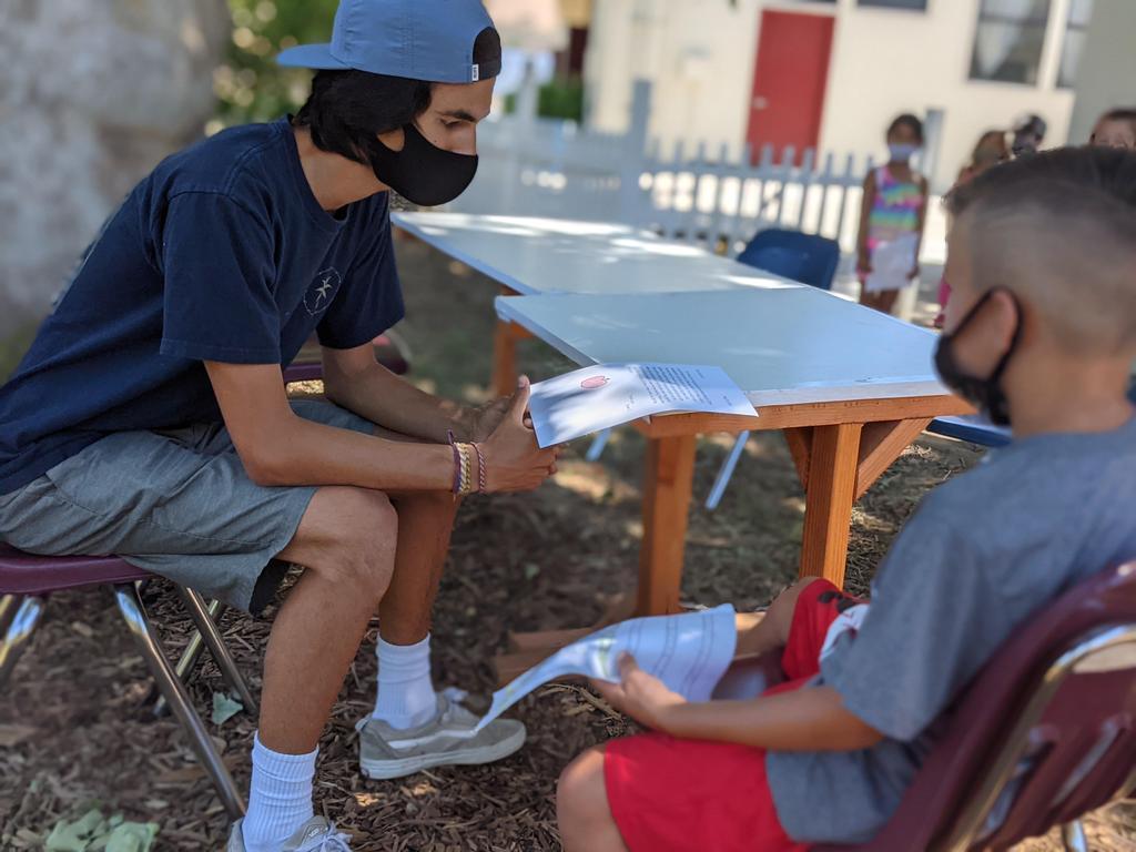 8th grader reading letter to Kinder Student