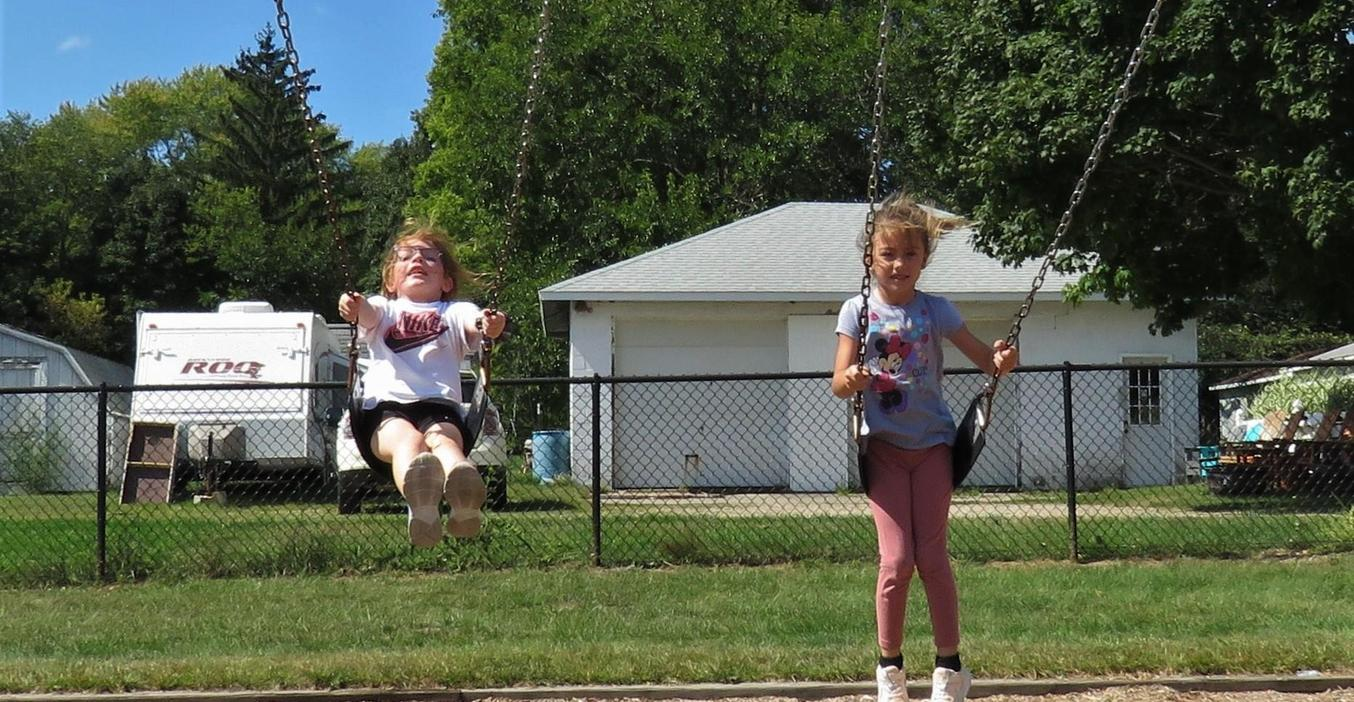 Two McFall students swing on a beautiful day on the playground.