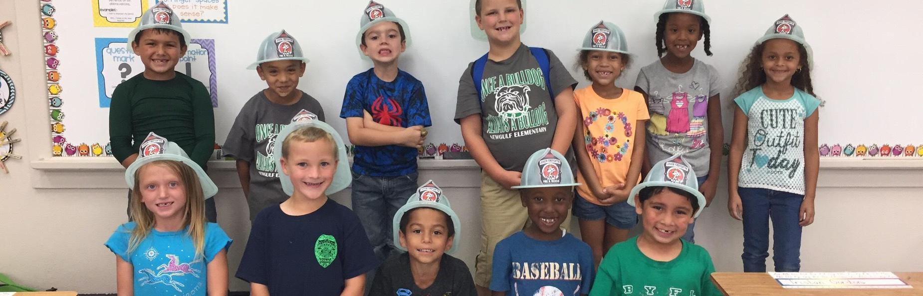 Children wearing firemen helmets