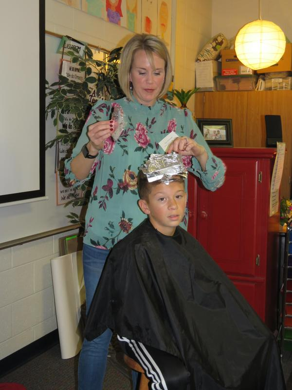 Fifth-grader Isaiah Boafo volunteers to get some bright colors added to his hair.
