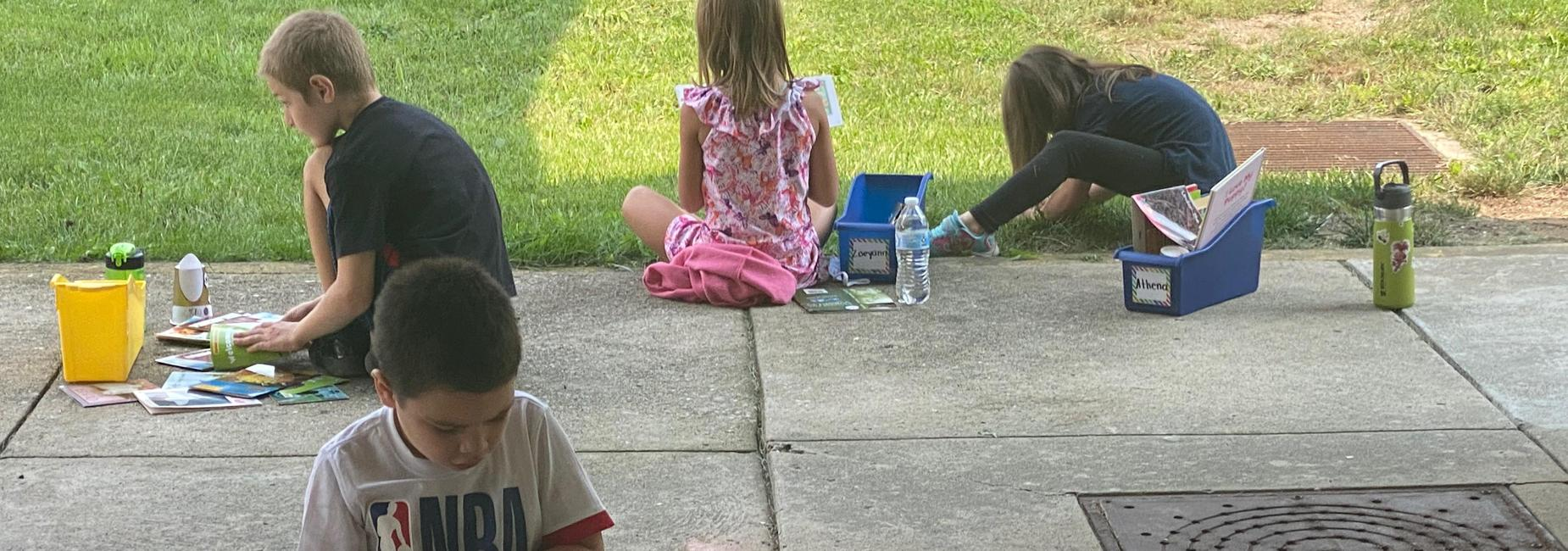 Students enjoy the nice weather to take a reading break outside.