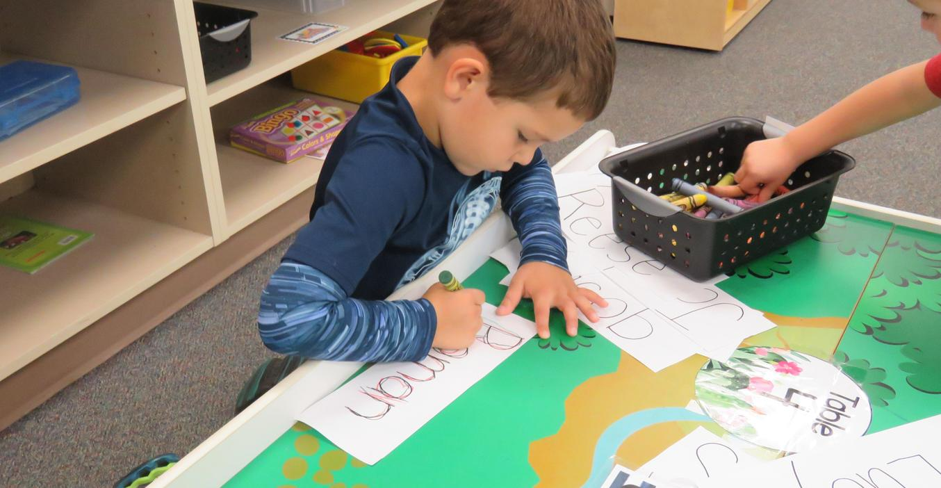 A Young 5 student practices writing his name.
