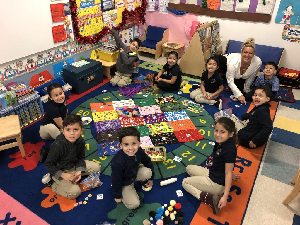 Ms. Hennessey's Class sitting on the class rug smiling