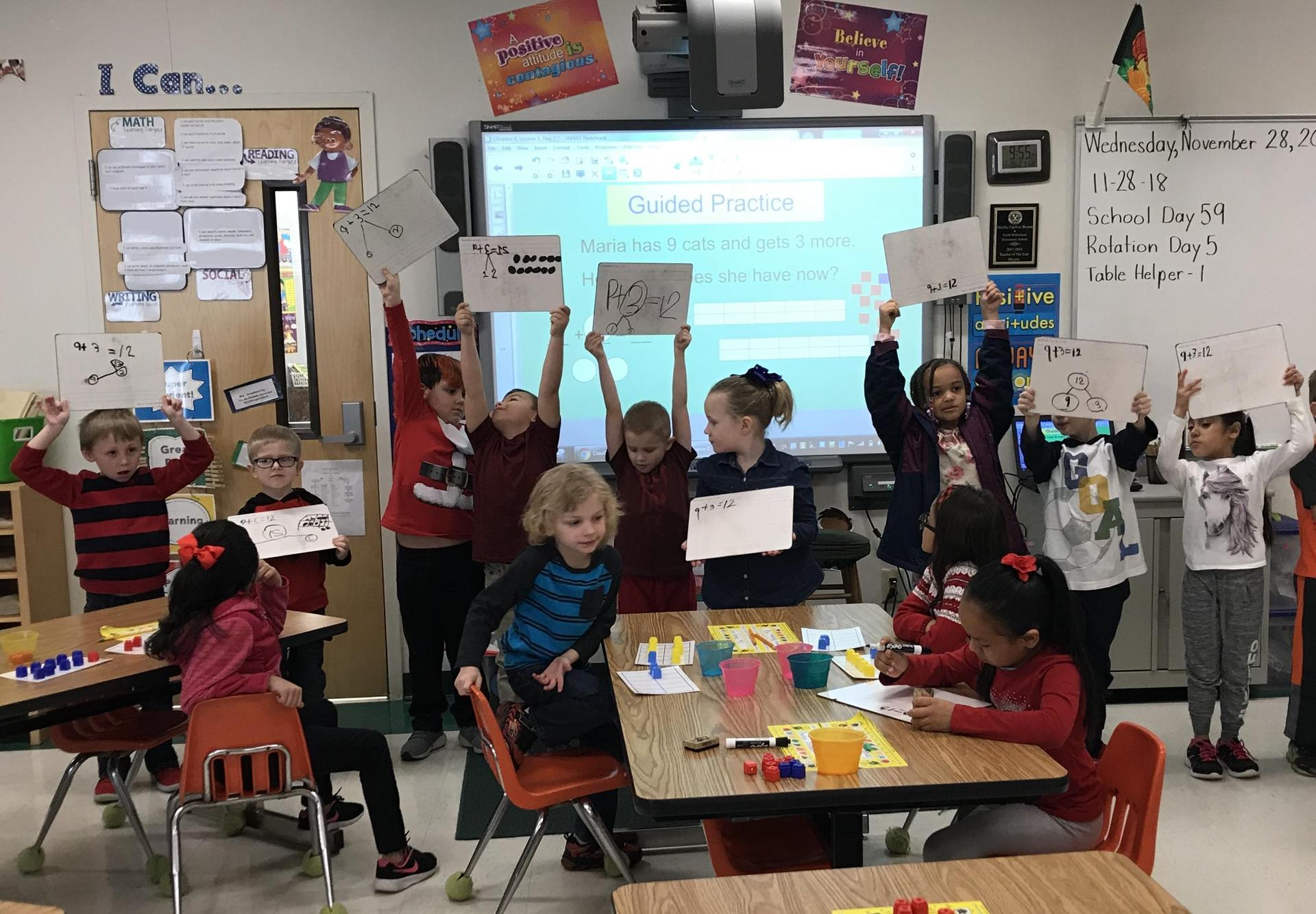 Students at the front of the room holding up signs during Math class