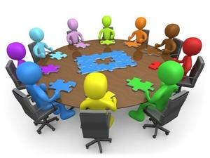 cartoon image people sitting around a circular table putting puzzle pieces together
