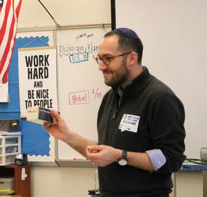 During a visit on Jan. 17 to a Westfield High School Comparative Religions class, Rabbi Ethan Prosnit of Temple Emanu-El explains the use of a Tzedakah box as part of the Jewish faith's commitment to acts of loving kindness, including collecting money for others in need.