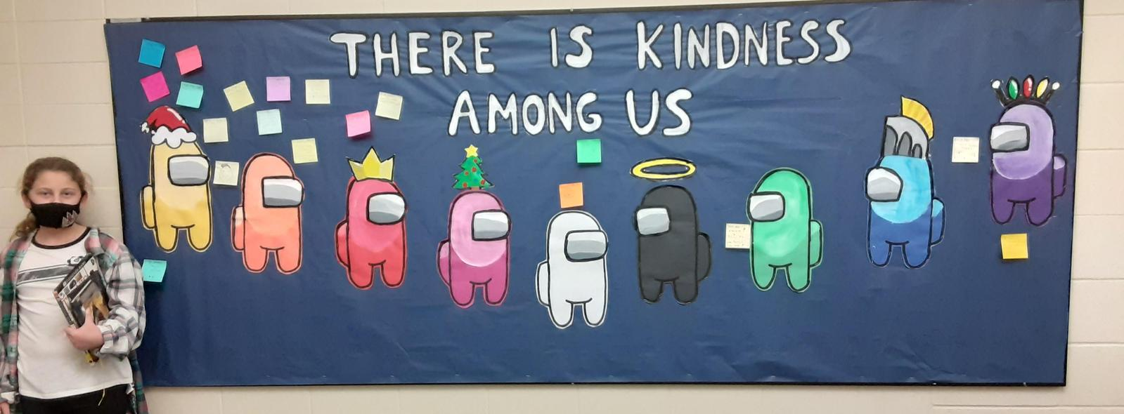 girl standing next to board that says There is Kindness Among Us