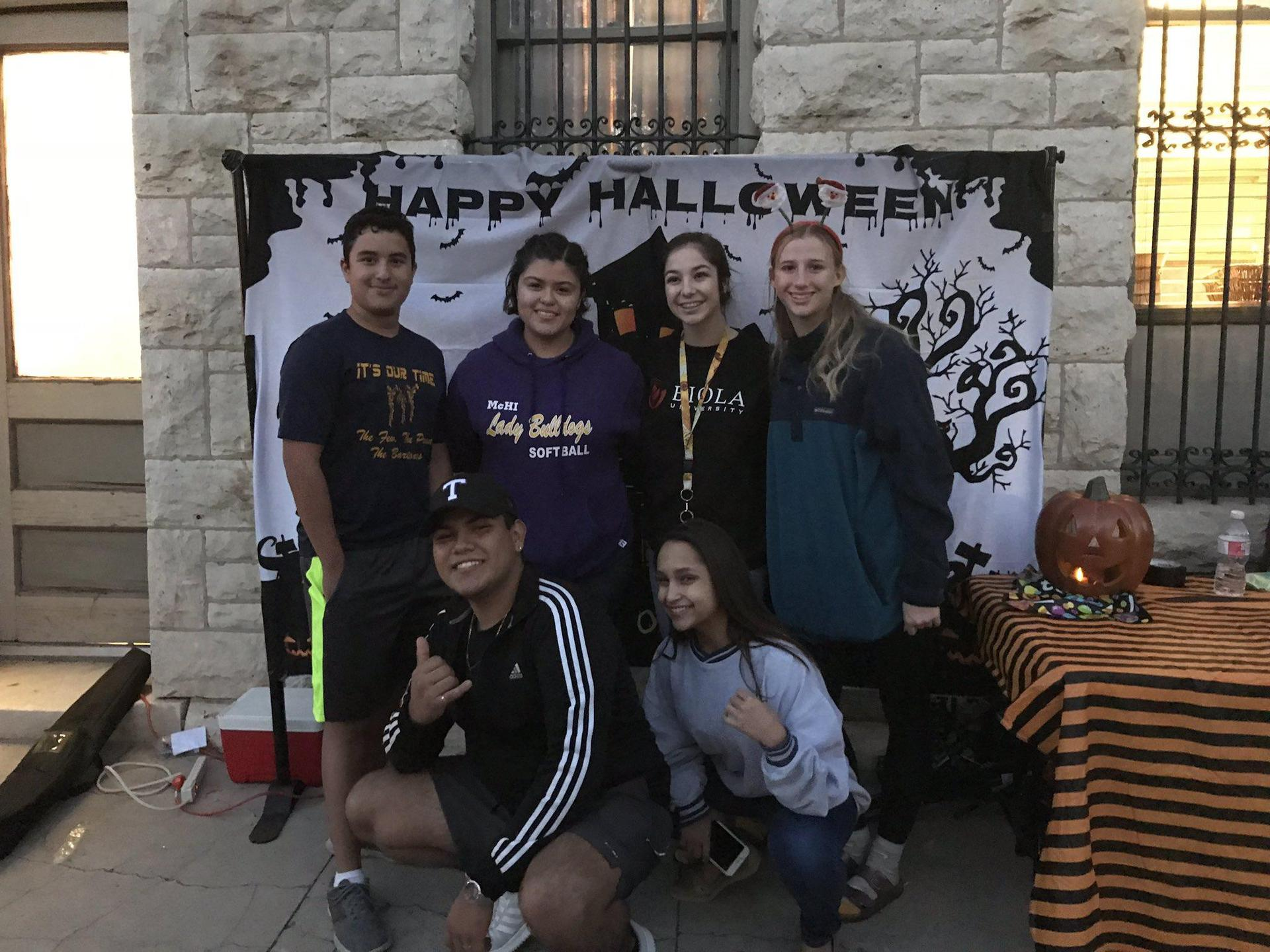 students posing in front of Halloween banner