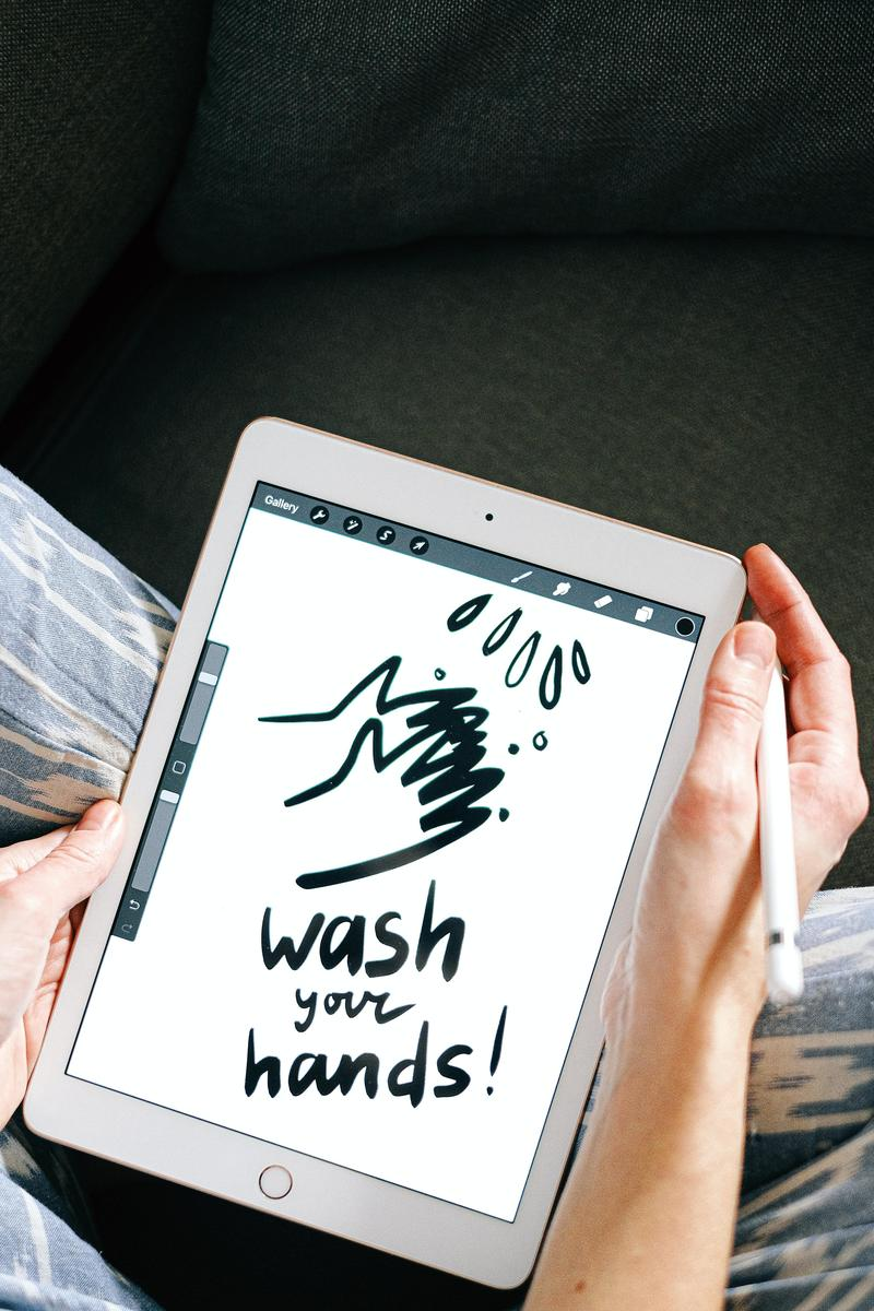 Ipad with drawing on it that says wash your hands with sketched image of hands washing