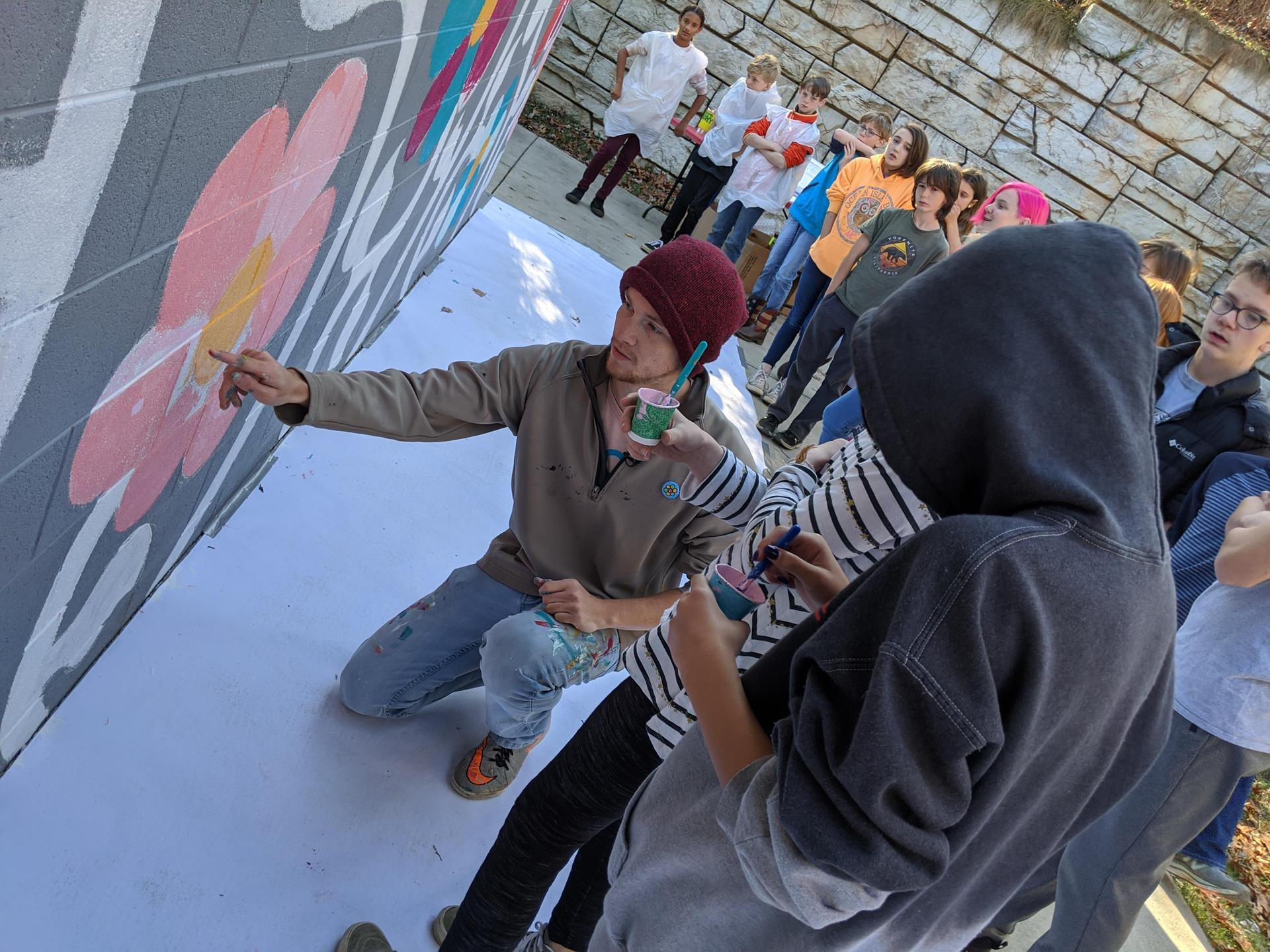 A volunteer helps a student paint