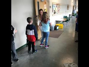 Mrs. O'Kelley is greeting her students as they enter her classroom