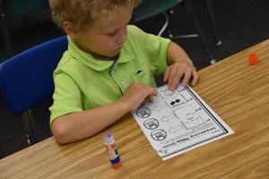 A blonde kindergarten student working on a handout.