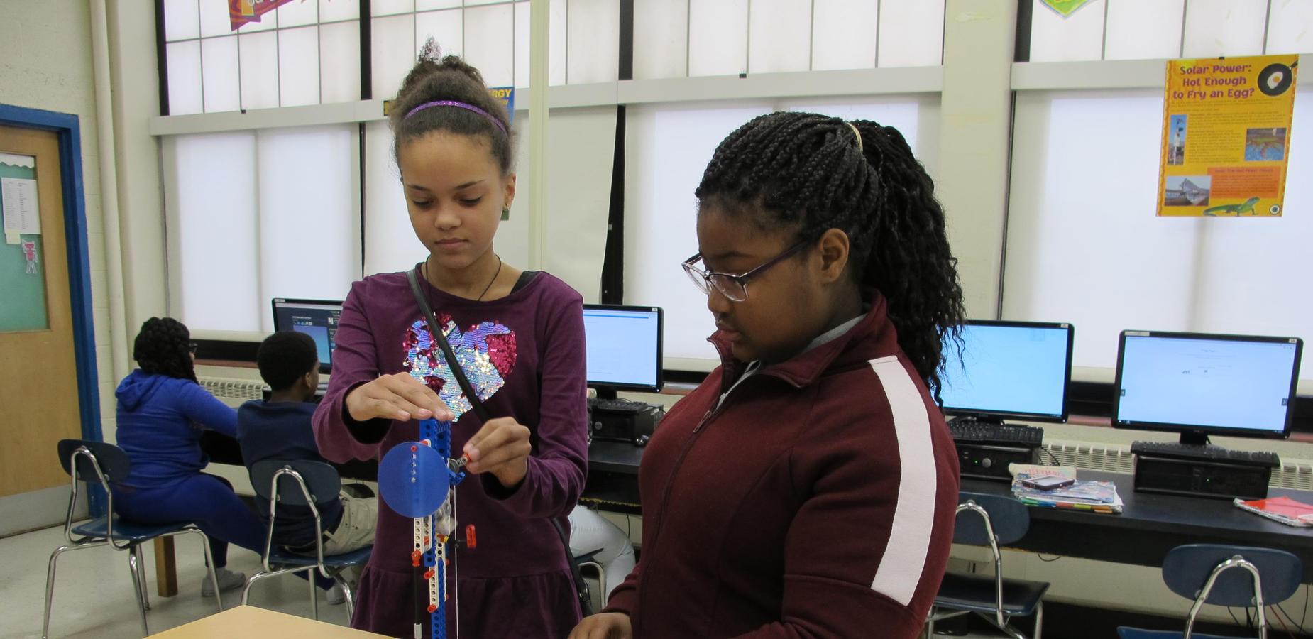 Two female students making adjustments to their Lego Robotics project