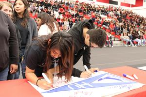 Students sign college poster