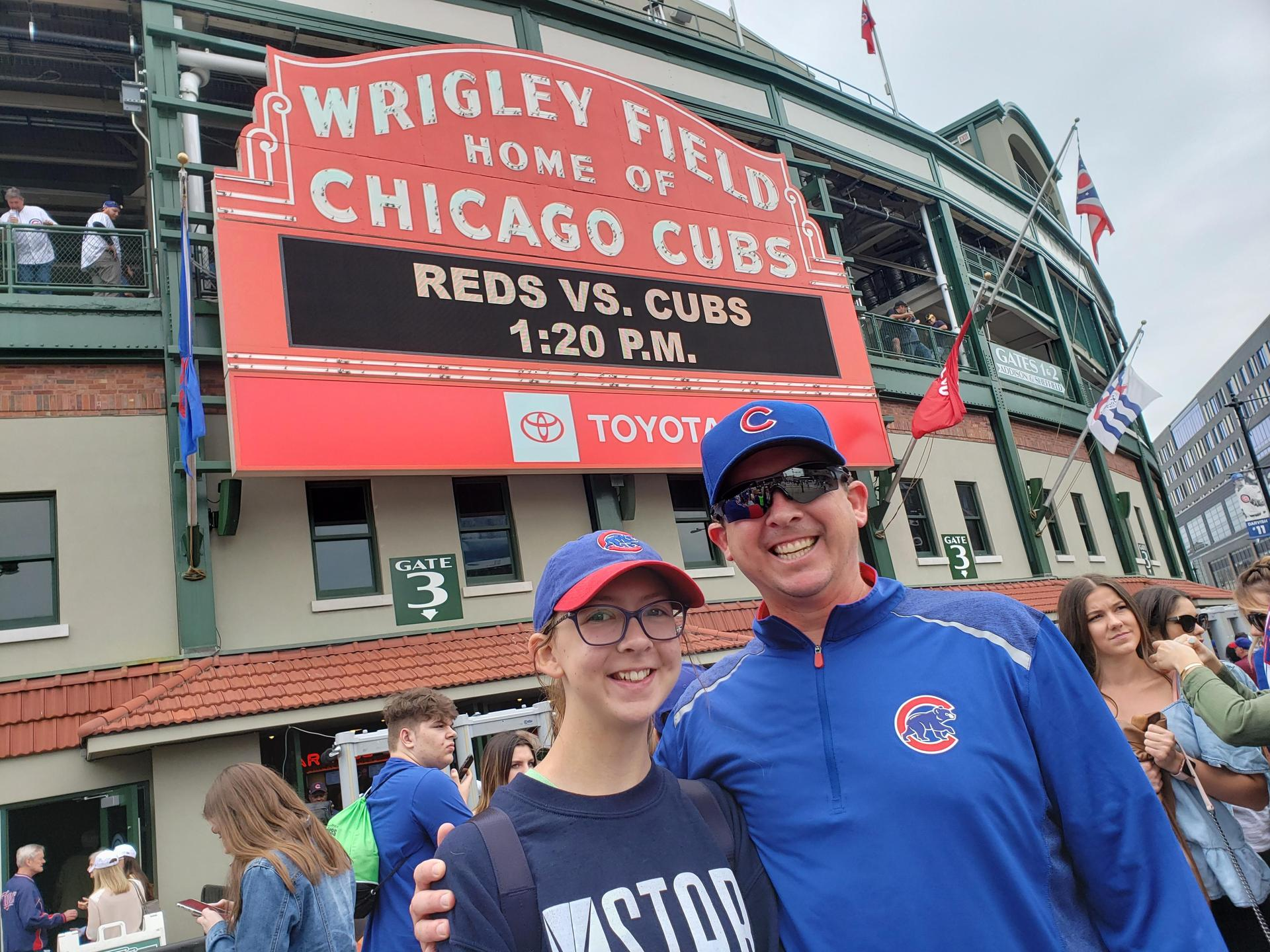 man and woman pose in front of Wrigley Field sign