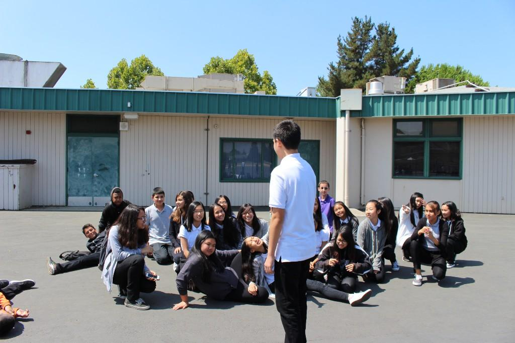several students sit on the blacktop while one student stands and speaks to the group