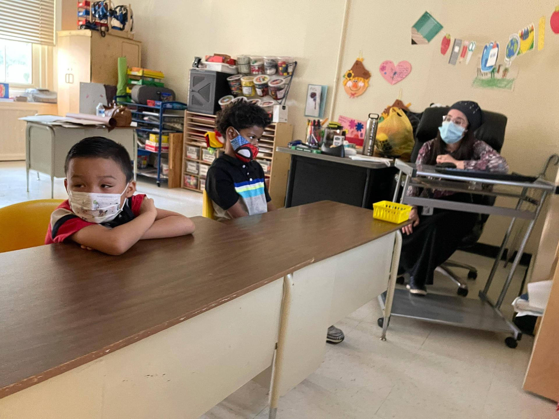 2 students sit at a desk with their masks on