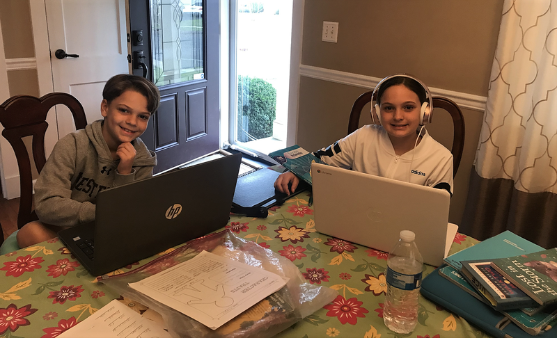 Photo of two Jefferson students with laptops at home during distance learning