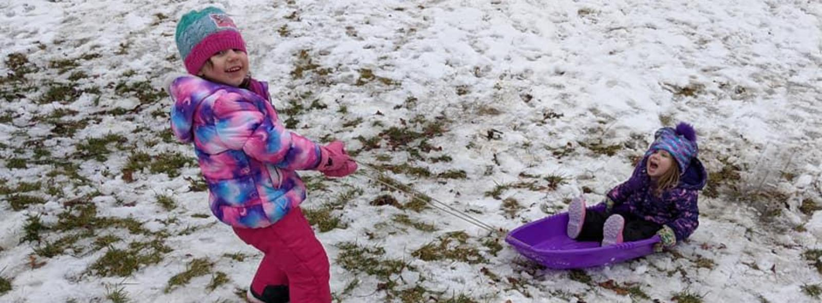 Two kids playing in the snow outside