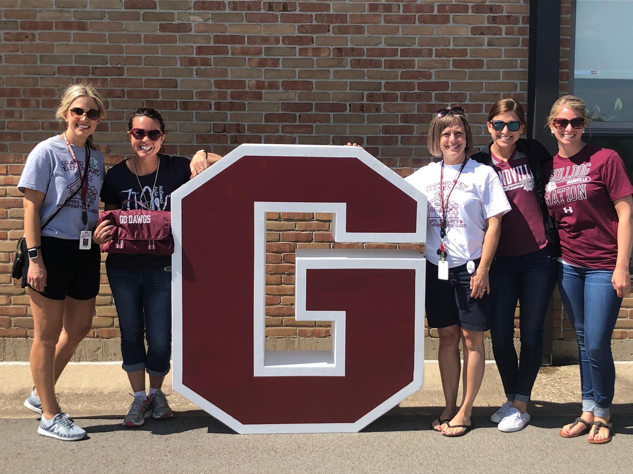 5 teachers stand by big G outside of school