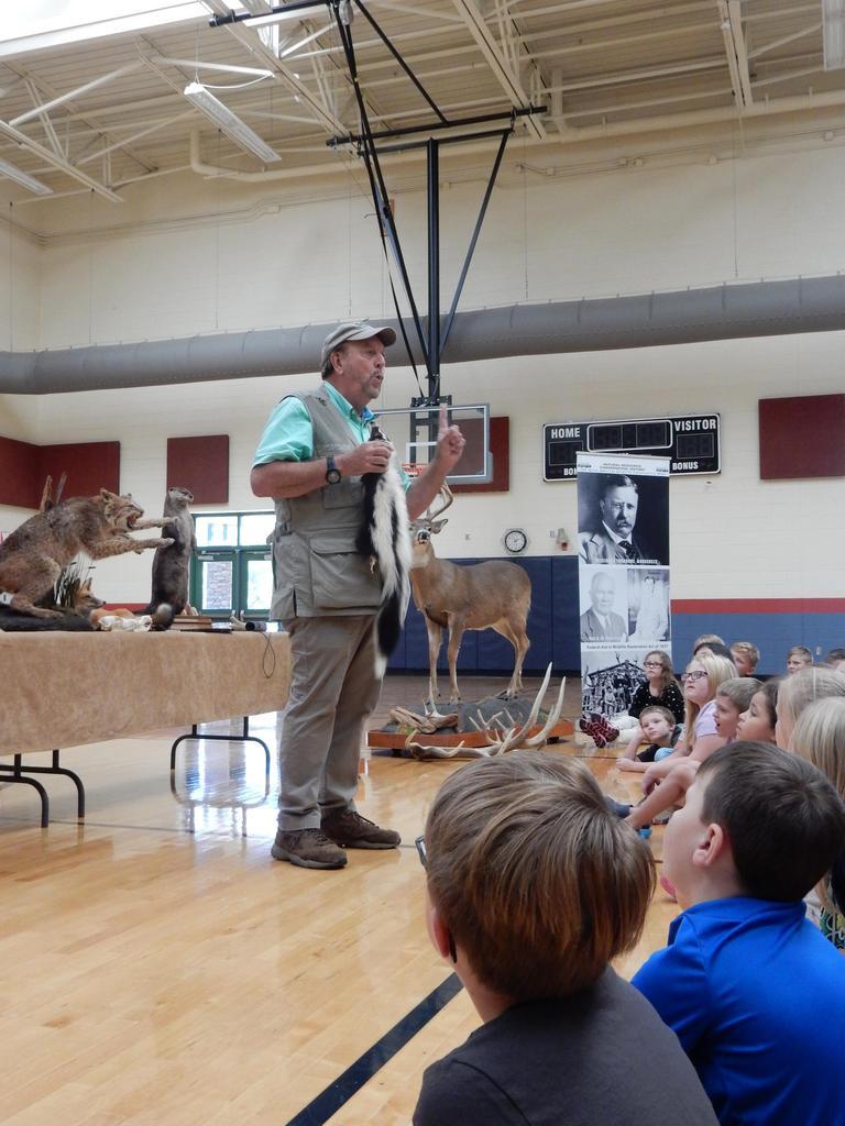 Representative holding skunk pelt speaks to students