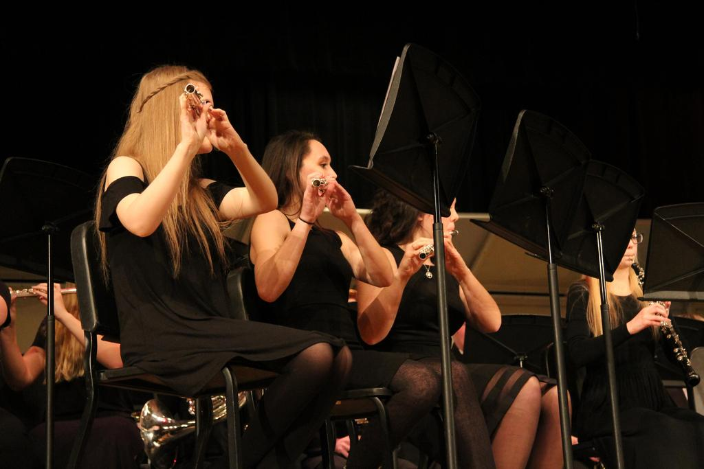 Three young ladies dressed in black and playing flutes