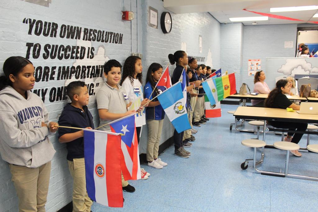 group of children standing up and holding their native flag