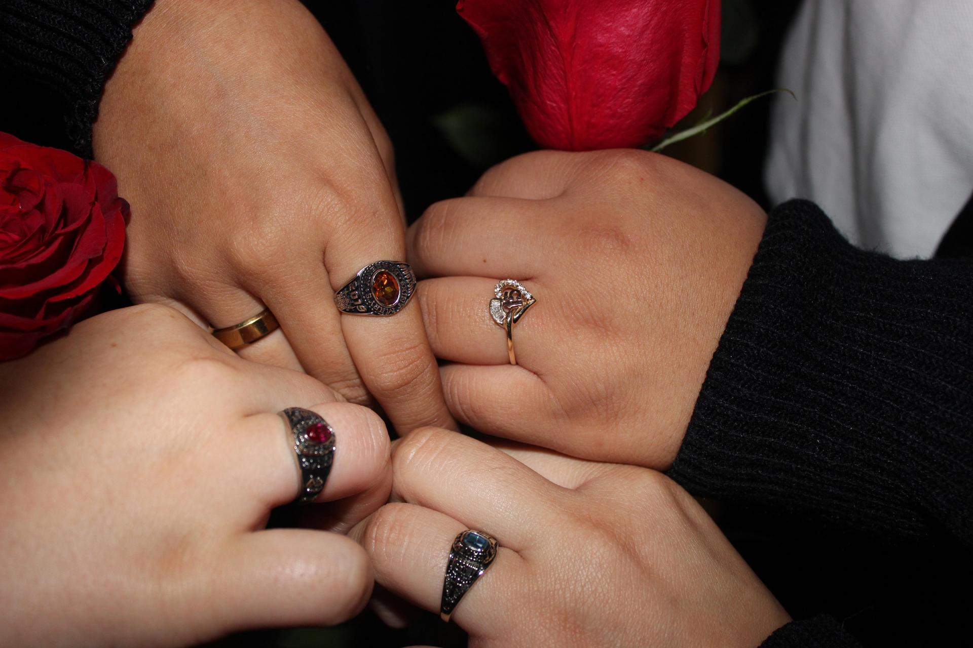 group of 4 students' hands with rings