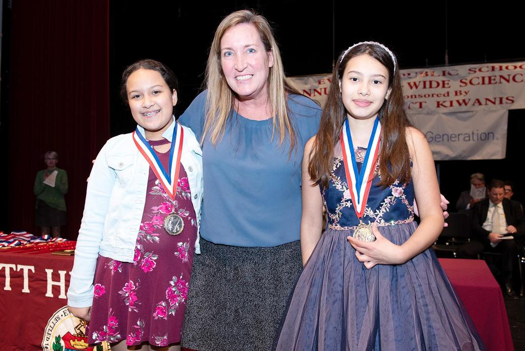 Ms. Grace presents medals two two sixth graders