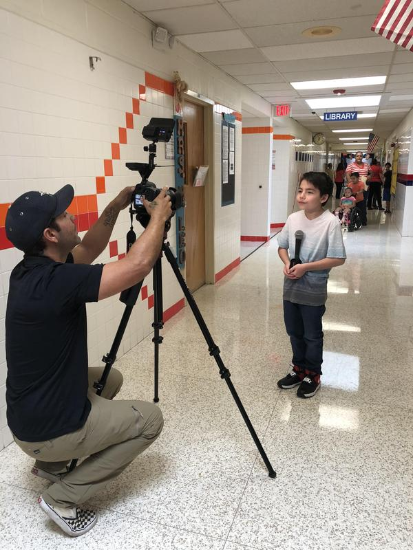 Student being interviewed by crew in the hallway.