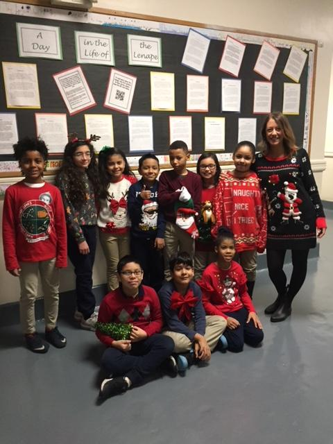 3rd grade teacher in hallway with her class showing off their ugly xmas sweaters