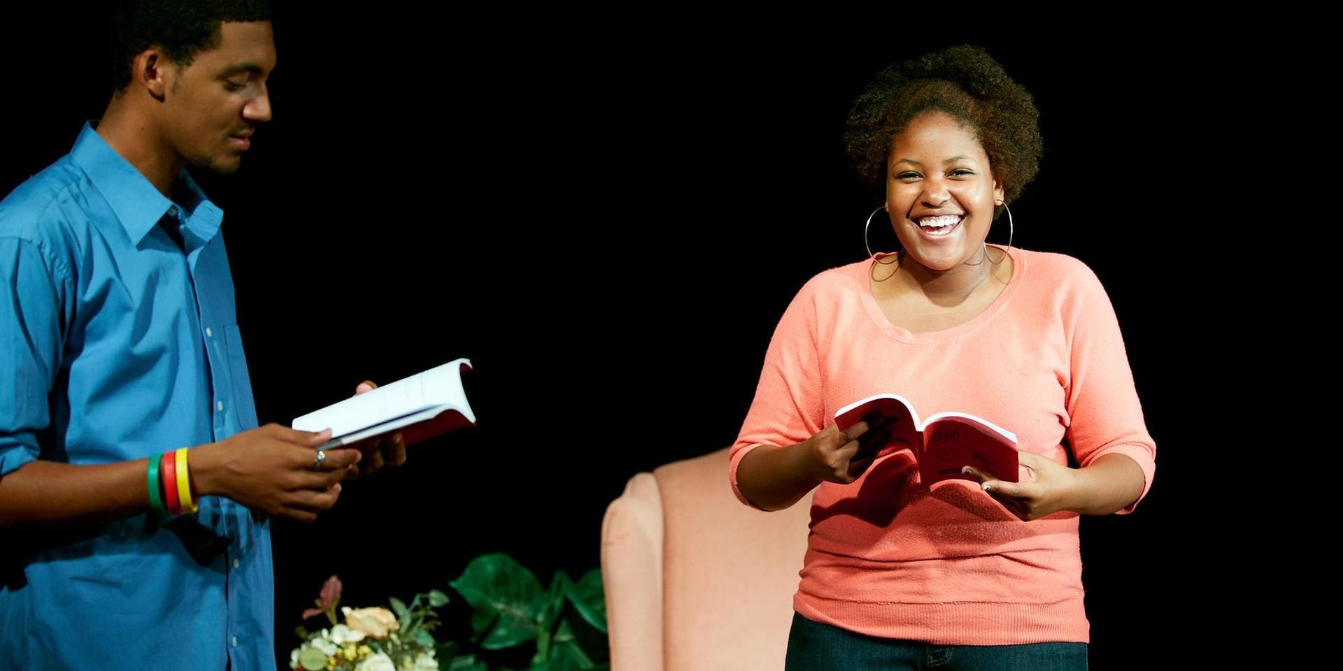 Two students rehearse a scene using scripts.